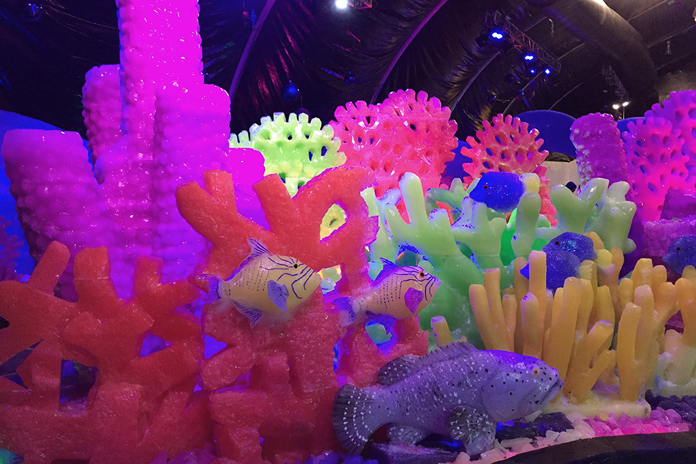 A colorful reef scene carved from ice. It includes bright red, pink, green and yellow sponges and coral, as well as colorful reef fish and a grouper.