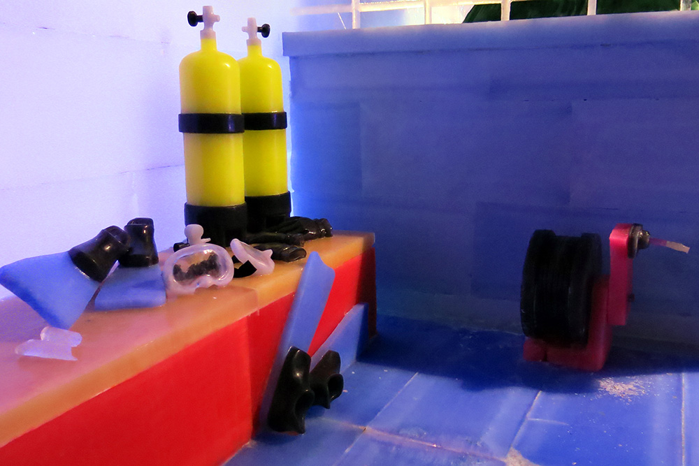 Ice replicas of two sets of scuba gear, including tanks, masks, fins, and gloves, arranged on a bench of the ice R/V MANTA. An ice replica of a small winch is also visible on the deck.