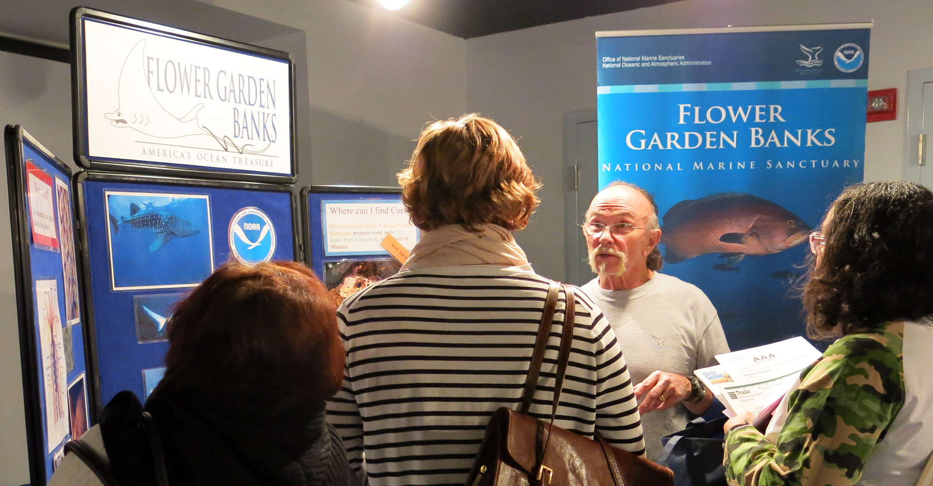 Volunteer talking to visitors at a sanctuary display booth