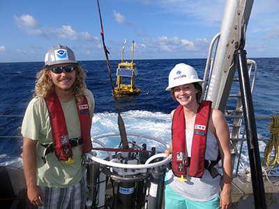 A man and a woman wearing hardhats standing next to research equipment on the deck of a boat with the ocean in the background