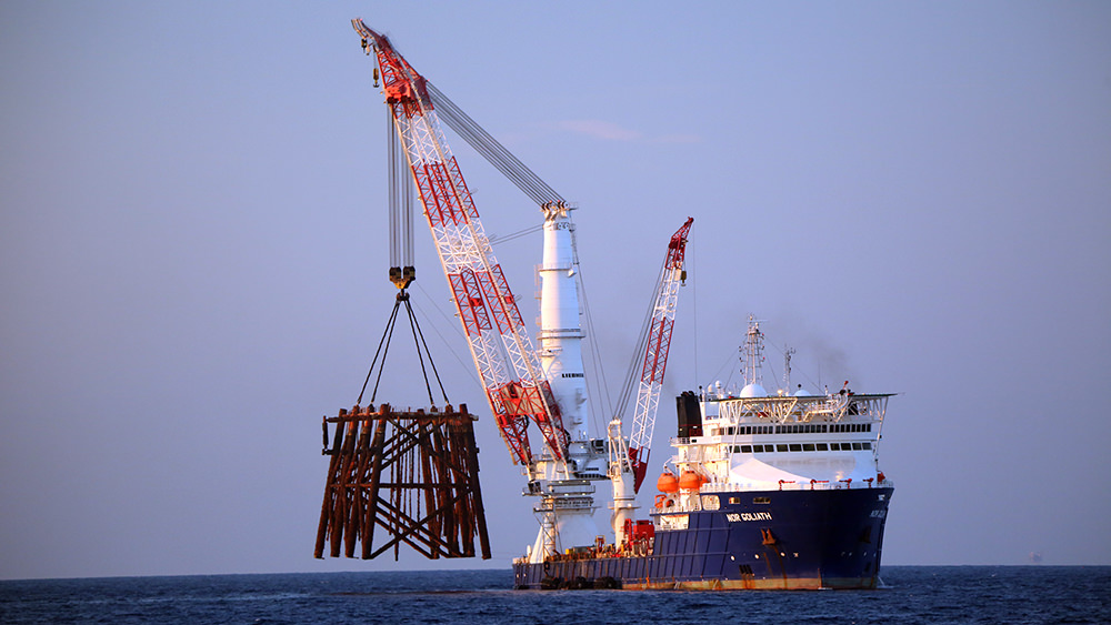 Large ship with crane hoisting the top section of a gas platform out of the water