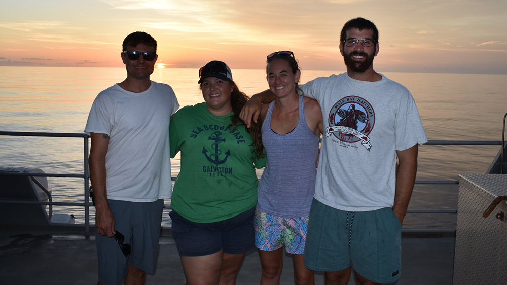 R/V MANTA crew standing on the deck at sunset.